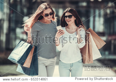 Beautiful girls in sun glasses are holding shopping bags  using a smart phone and smiling while standing outdoors