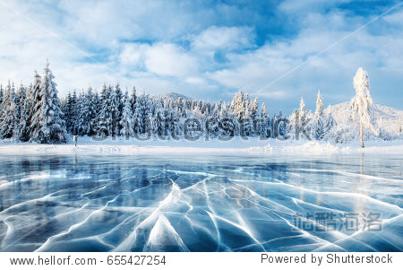 Blue ice and cracks on the surface of the ice. Frozen lake under a blue sky in the winter. The hills of pines. Carpathian  Ukraine  Europe