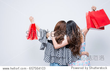Sale Consumerism and people concept - happy young women with shopping bag Back of a couple of young girl have funny shopping Girls with shopping bags Young women doing some shopping Age 20-30 years.
