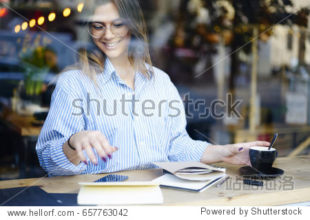 Cheerful young attractive journalist in eyeglasses enjoying coffee break in cafe sitting near window screen  female creative manager doing paperwork satisfied with successful media marketing project