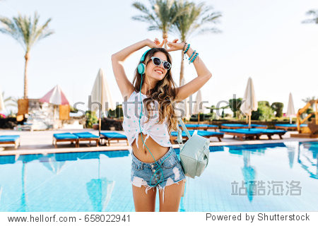 Amazing shapely girl in white blouse dancing with hands up  while listening positive music near the pool. Young tanned woman in headphones and sunglasses having fun on palm trees background