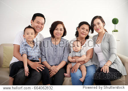 Portrait of big Asian family posing for photo at home  all smiling happily looking at camera