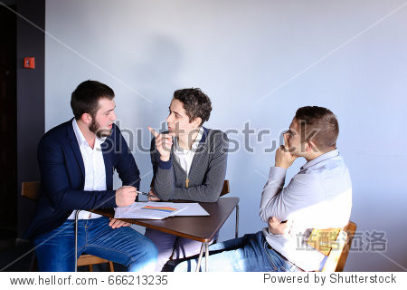 Three young men who are held discuss important questions about work and general business. Guy with curly hair talking on phone and hands receiver to seated man  who then conducts dialogue on mobile