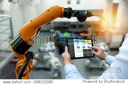 Engineer hand using tablet  heavy automation robot arm machine in smart factory industrial with tablet real time monitoring system application. Industry 4th iot concept.