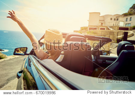 Back view of blonde in straw hat driving cabriolet with blue sea and houses on background.