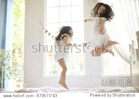 happy family at home. sisters jumping on the bed  playing and laughing