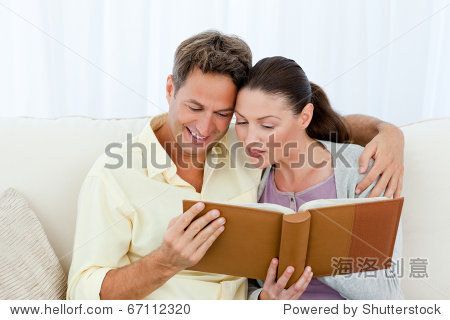 Attentive man and woman looking at a photo album on the sofa in the living room