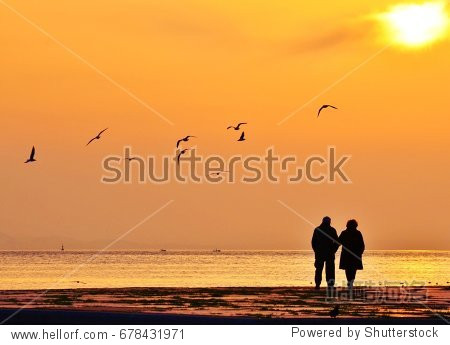 Old couple walking near the sea at sunset. The Sun between clouds and seagulls flying on the sea  silhouette.
