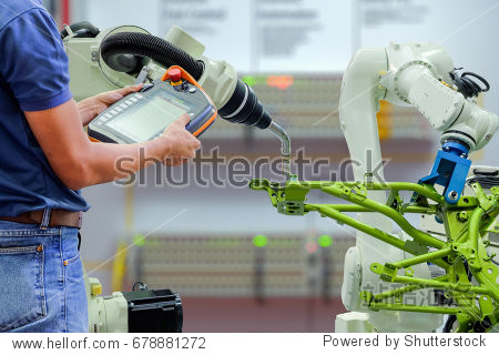 Engineers use a wireless remote control of robotic welding and robot workpiece for smart factory  industry 4.0 concept