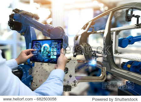 Engineer hand using tablet with machine real time monitoring system software. Automation robot arm machine in smart factory automotive industrial Industry 4th iot   digital manufacturing operation.