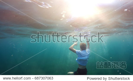 young man sinking into the sea