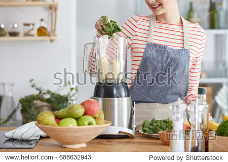 Woman making healthy smoothie with bananas and kale