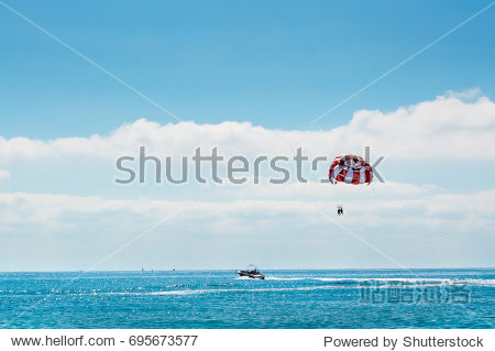 Sea parasailing water amusement. Flying on a parachute behind a boat on a summer holiday by the sea in the resort Bulgaria on background a blue sky with clouds.