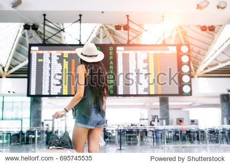 Asian young hipster woman in international airport looking at the flight information board  checking her flight.Unrecognizable back
