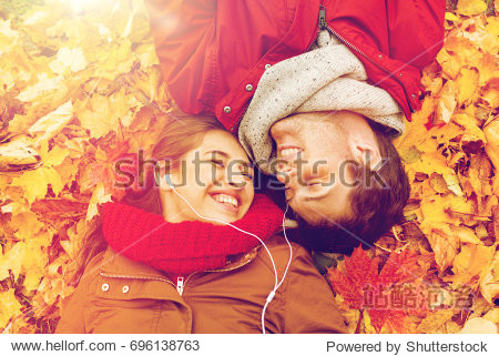 love  relationship  season  family and people concept - close up of happy couple with earphones listening to music and lying on autumn leaves