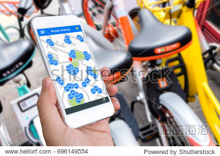 Bicycle sharing service or rental technology concept. Sharing economy and collaborative consumption. Customer hand using mobile phone to find bicycle for ride.