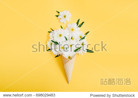 Waffle cone with chamomile flower bouquet on yellow background. Flat lay  top view floral background.