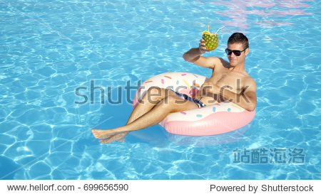 CLOSE UP: Smiling guy sitting on doughnut floatie drinking pineapple cocktail