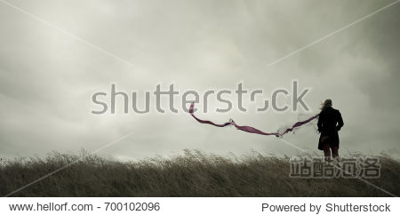 Woman standing alone in harsh weather with dramatic sky