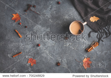 Autumn composition. Cup of coffee  blanket  autumn leaves  cinnamon sticks on black background. Flat lay  top view.