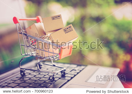 Online shopping and delivery service concept. Paper cartons in a shopping cart on a laptop keyboard  this image implies online shopping that customer order things from retailer sites via the internet.