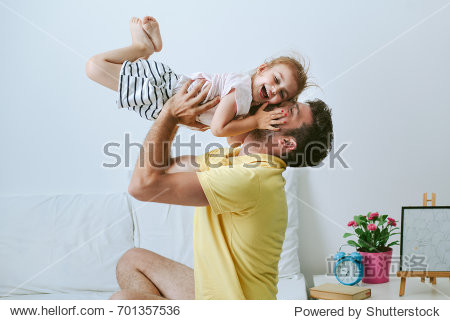Loving and caring dad playing with his daughter at home. Father lifting little girl