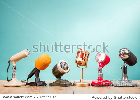 Retro old microphones for press conference or interview on table front gradient aquamarine background. Vintage old style filtered photo