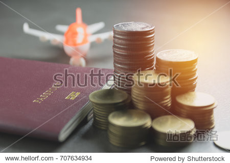 Closeup stack coin with passport and air plane model. Financial and saving concept.