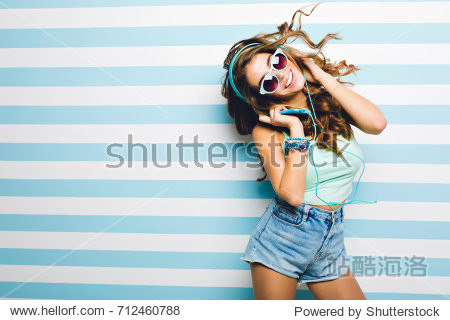 Slim laughing girl in trendy denim shorts funny dancing holding big headphones. Attractive tanned young woman in sunglasses with curly hair waving chilling on striped background and smiling.