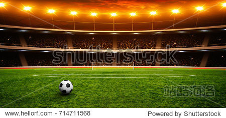 Soccer ball on green stadium  arena in night illuminated bright spotlights