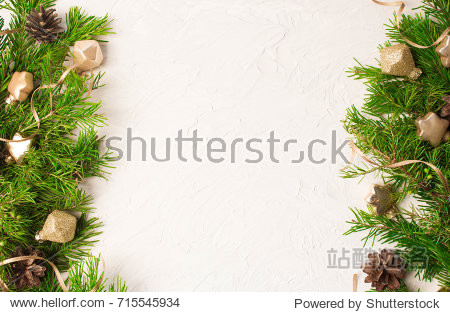 Christmas or New Year background: fir tree branches  gold glass balls  decoration and cones on a white plaster background
