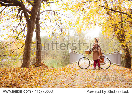 travel concept young woman walk with bicycle picnic set hot drinks in bright autumn city park background copy space