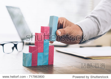 Businessman working at office desk  he is building a growing financial graph using wooden toy blocks: successful business concept