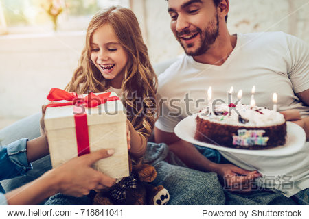 Good morning  birthday girl! Little cute girl and her parents are sitting on bed with presents and cake in hands.