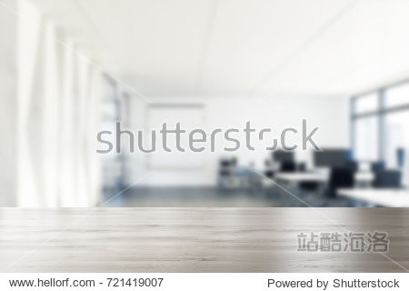 Side view of an open space office environment with rows of computer tables standing near a panoramic windows. 3d rendering mock up blurred