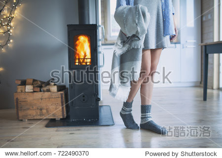Young woman wearing winter socks standing home holding a blanket by the fireplace. Wooden cabin interior.
