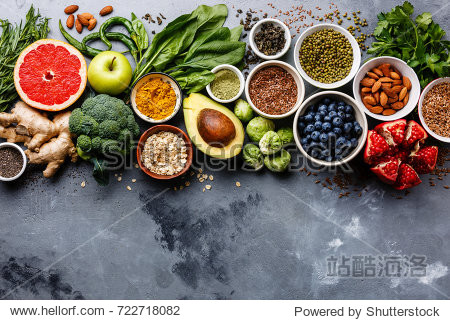 Healthy food clean eating selection: fruit  vegetable  seeds  superfood  cereals  leaf vegetable on gray concrete background copy space