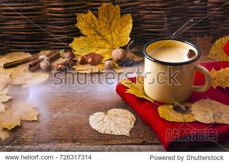 Coffee in an enamel mug with a woolen scarf  leaves  nuts  cinnamon sticks and star anise on wooden background. Autumn cozy background.