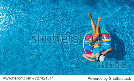 Aerial top view of beautiful girl in swimming pool from above  relax swim on inflatable ring donut and has fun in water on family vacation