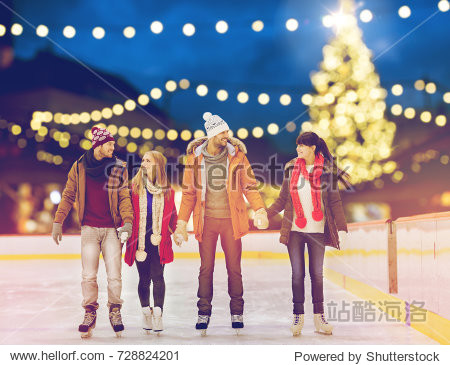 christmas  winter and leisure concept - happy friends holding hands on skating rink over outdoor holiday lights background