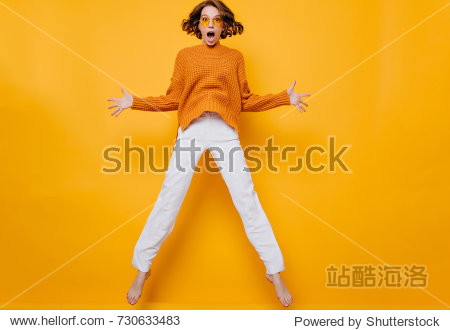 Full-length portrait of funny woman in white pants fooling around on yellow background. Barefooted curly girl in sunglasses and soft sweater jumping and waving hands with shocked face expression.