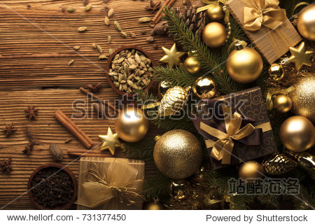 Christmas decoration in golden and brownish aesthetics with presents in boxes  golden baubles  christmas spices all on a rustic wooden background with copy space.