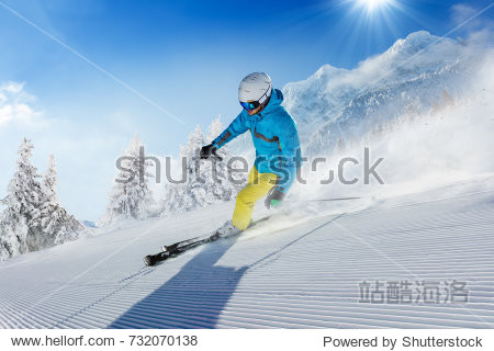 Young man skier running down the slope in Alpine mountains. Winter sport and recreation  leisure outdoor activities.