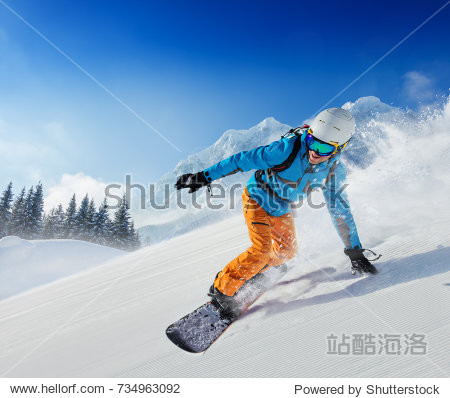 Young man snowboarder running down the slope in Alpine mountains. Winter sport and recreation  leisure outdoor activities.