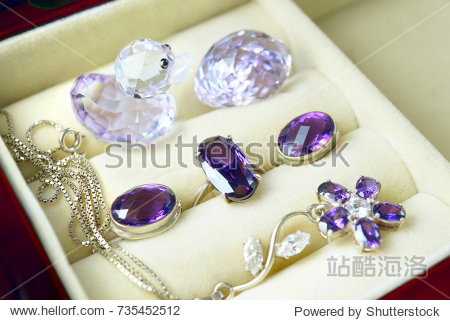 A set of silver jewelry in a box. Ring  earrings and pendant in the form of a flower with purple jewels amethyst close-up macro with soft focus.