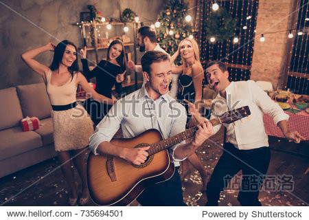 Celebrating newyear. Young handsome musician makes a noise with his instrument! Group of beautiful festive youth on luxury feast  many glitters on floor  classy outfits  Chilling relax mood all night