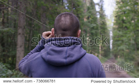 Athlete on road through forest. Back view. Athletic man on road through forest. Athletic man standing on trail through autumn forest