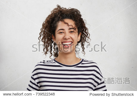 Positive emotions concept. Emotional happy young woman with crisp hair  appealing appearance and broad charming smile  rejoices her success or being glad to organize unforgettable party with friends