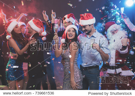Young couple dancing with glasses of champagne in hands. Behind them dance their friends and a man dressed as Santa Claus. Against the background of colored smoke  confetti flies around.