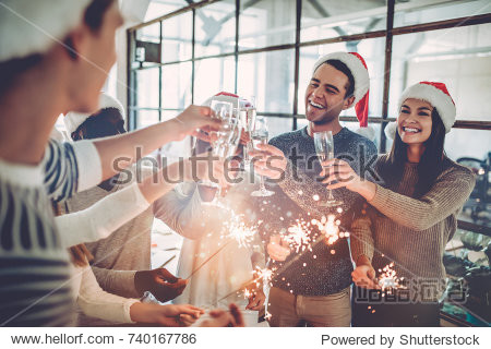 Merry Christmas and Happy New Year 2018! Multiracial young creative people are celebrating holiday in modern office. Group of young business people are drinking champagne in coworking.